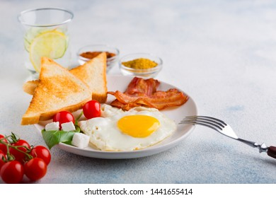 Fried egg with bacon, toast, tomatoes and a glass of mineral water with lemon and cucumber on a white background. English breakfast. with copy space for your text