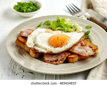 fried egg, bacon and toasted bread on plate