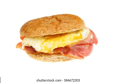 Fried egg and bacon in a wholemeal bread roll isolated against white
