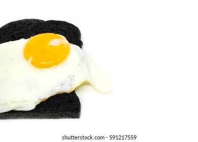 fried egg and Black charcoal toast bread on white background