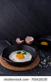 fried egg in black pan and ingredient on dark background