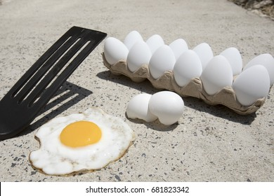 Fried egg with broken shells and carton of white eggs on hot sidewalk on summer day.