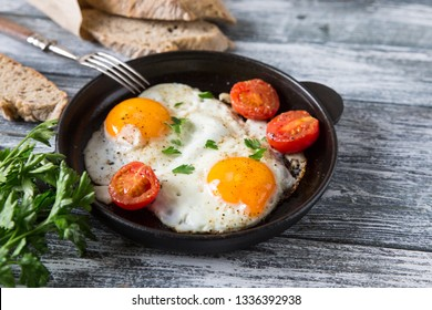 Fried egg. Close up view of the fried egg on a frying pan with cherry tomatoes and parsley.