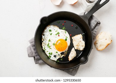 Fried egg for delicious healthy easy breakfast on a table. Fresh homemade meal on a frying pan.