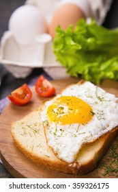 fried egg with dry dill and vegetables on wooden plate