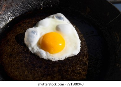 fried egg in a frying pan with a huge yolk, cooking fried eggs, one egg