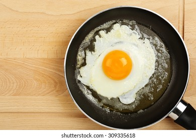 fried egg in frying pan on wooden surface