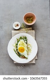 Fried egg, green aspargus, feta cheese and micro greens spring sandwich on plate over light concrete background. Healthy eating, slimming, diet lifestyle concept. Flat lay, top view