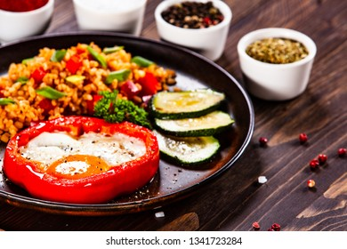 Fried egg, groats and vegetables on wooden table
