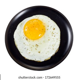 Fried egg on black plate isolated on white background