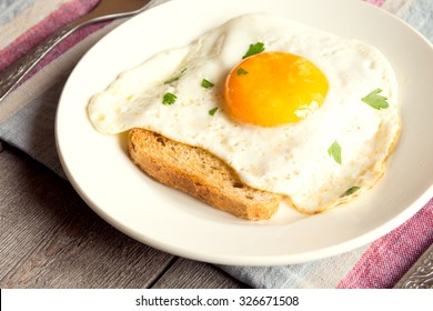 Fried egg on bread for breakfast on plate and rustic table