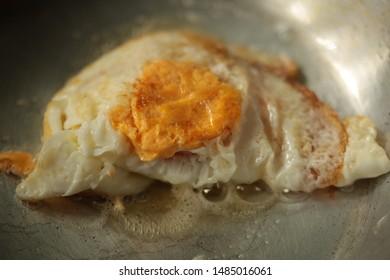 Fried egg on frying pan.