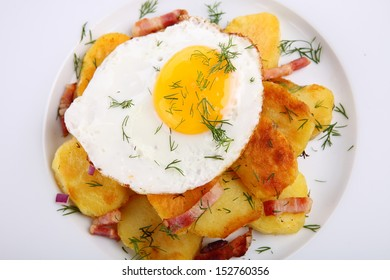 Fried Egg on a heap of roasted Potatoes on wooden background
