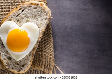 Fried egg on heart-shaped slice of bread.
