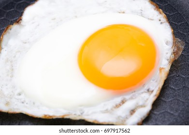 Fried egg on pan, out focus