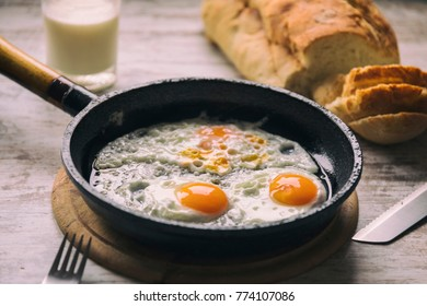 Fried egg on a pan served with homemade bread
