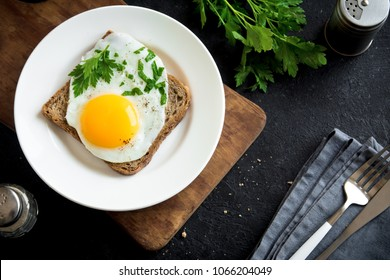 Fried Egg on Toast  for Breakfast. Fried egg with bread and parsley on white plate on black, top view, copy space.