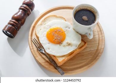 fried egg on toast, coffee on white background