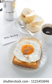 """fried egg on toast, fruit, black coffee and text """"Hello Sunday"""""""