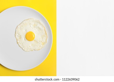 Fried egg on white round plate with split color yellow/white background and copyspace.