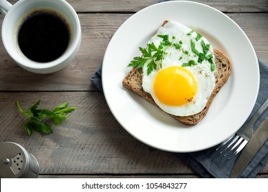 Fried Egg on Wholegrain Toast and cup of Coffee for Breakfast. Fried egg with bread on plate over wooden table, top view, copy space.