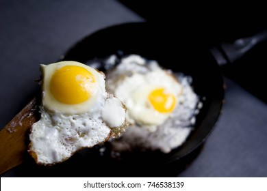 fried egg on a wooden spatula, large yolk, cooking fried eggs,
