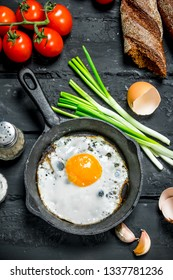 Fried egg in a pan with bread and tomatoes. On black rustic background.