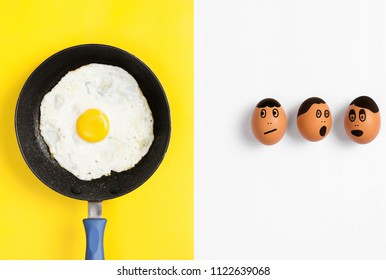 Fried egg in pan with faces drawn on uncooked eggs looking worried, Flat lay food image