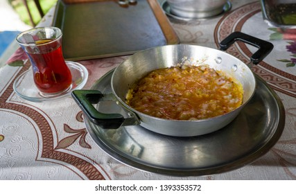 """Fried egg in pan and Turkish tea on table. Breakfast preparation concept. Traditional Turkish brewed tea drink in morning also as known """"Cay"""" or """"Turk Cayi"""". Menemen with Turkish Tea."""