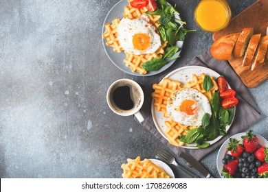 Fried egg, spinach, waffles and cup of coffee espresso, bread, baguette on dark  background, flat lay, top view, copy space