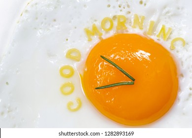 Fried egg sunny side up in form of a clock with noodle letters for good morning