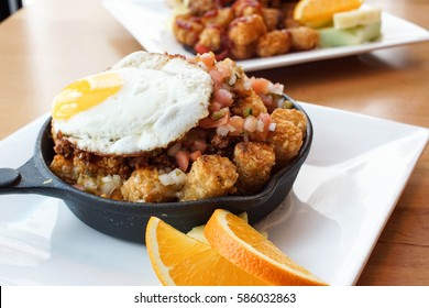 fried egg, sunny side up on a bed of potato tots with spicy sausage, cheese and onions served on a personal sized frying pan for breakfast special at a restaurant