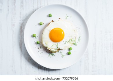 fried egg with toasted bread decorated with green pea on white plate. breakfast dish.