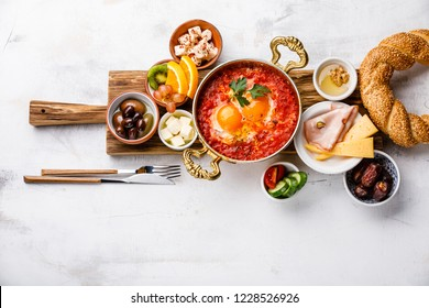 Fried egg with tomatoes in copper pan and various snacks for Breakfast on white background copy space
