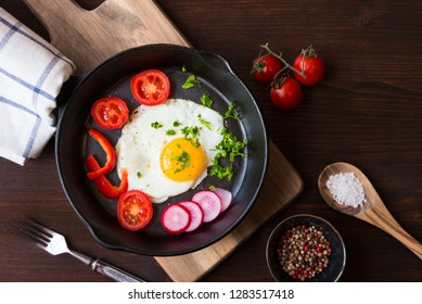 Fried egg with vegetables on a frying pan for breakfast on dark wooden table