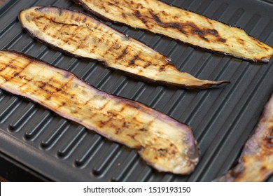 Fried eggplant or aubergine on electric grill, top view. Grilled vegetarian vegetables. Close up