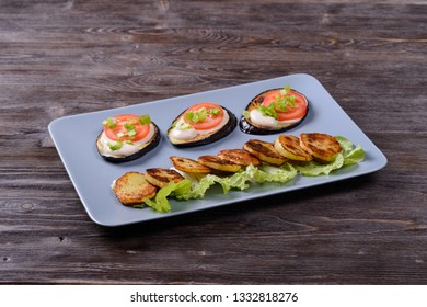 fried eggplant and potatoes with tomato and salad on a plate