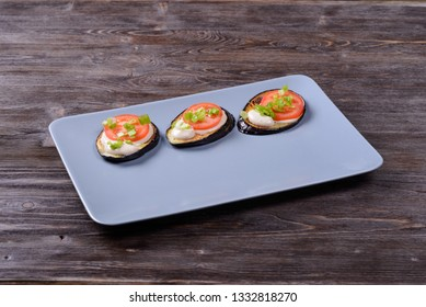 fried eggplant with sauce, tomato and onion on a plate