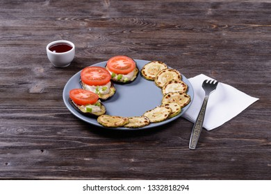fried eggplant with sauce, tomato, onion and zucchini on a plate