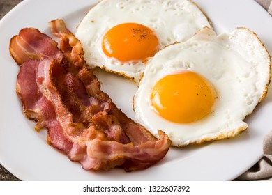 Fried eggs and bacon for breakfast on wooden table. Close up
