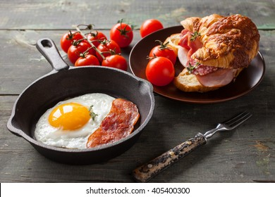 fried eggs with bacon and croissant with sausage on an old wooden background, selective focus