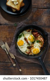Fried eggs with bacon in frying pan on dark wooden table with toasts, top view. Breakfast table concept