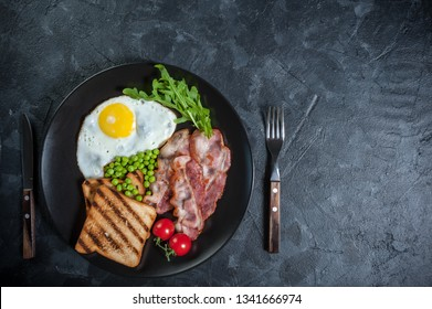 Fried eggs with bacon and green peas on breakfast, wooden rustic boards, food background. Flat lay