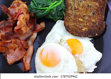 Fried eggs and bacon with a serve of spinach and toast.