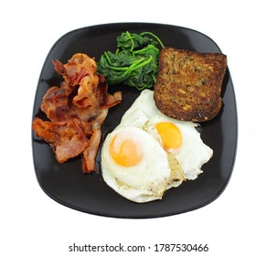 Fried eggs and bacon with a serve of spinach and toast over a white background