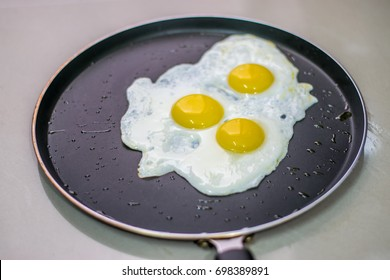 Fried eggs in a black non stick pan with little droplets of oil sprinkled making sunny side up of three eggs