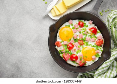 Fried eggs in black pan with ham, cherry tomatoes and spring green onions. Delicious Breakfast with toast and butter. The classic English lunch. Copy space