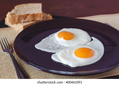 Fried eggs with bread on table - selective focus