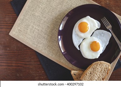 Fried eggs with bread on wooden table top view with copy space