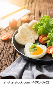 fried eggs and bread in the shape of a heart and fresh vegetables with blank notebook. Top view and wooden background